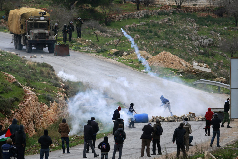 Description of . Palestinians throw tear gas canisters back at Israeli security forces during a weekly protest against the expansion of the nearby Jewish settlement of Halamish, in the West Bank village of Nabi Saleh near Ramallah, Friday, Feb. 1, 2013. (AP Photo/Majdi Mohammed)