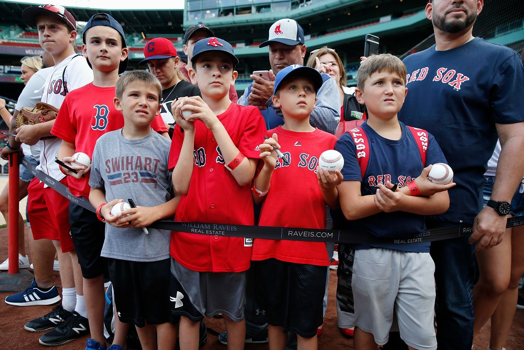 . Fans wait for autographs before a baseball game between the Boston Red Sox and the Cleveland Indians in Boston, Tuesday, Aug. 21, 2018. (AP Photo/Michael Dwyer)