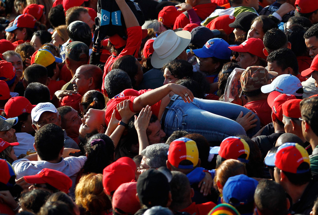 ". A supporter of Venezuela\'s late President Hugo Chavez is lifted out of the crowd after fainting while waiting for a chance to view his body at the military academy in Caracas March 8, 2013. Chavez will be embalmed and put on display ""for eternity\"" at a military museum after a state funeral and an extended period of lying in state, acting President Nicolas Maduro said on Thursday.   REUTERS/Carlos Garcia Rawlins"