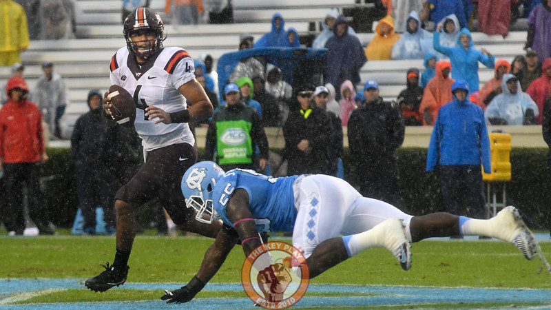 Virginia Tech quarterback Jerod Evans (4) scrambles past driving North Carolina defensive end Jason Strowbridge (55). (Michael Shroyer/ TheKeyPlay.com)
