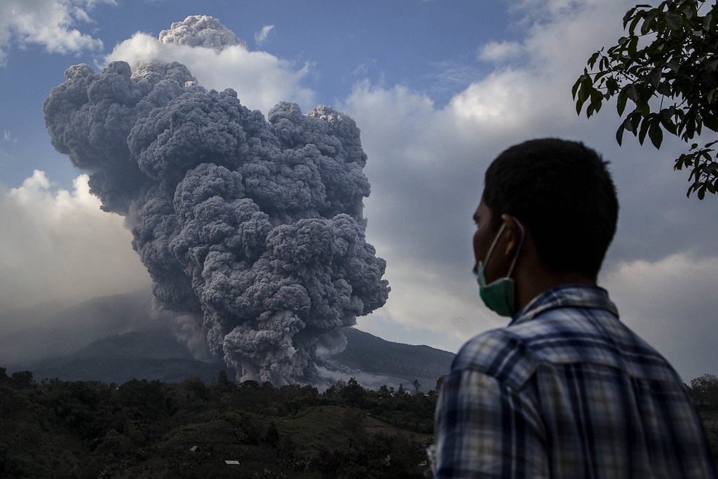 . A man watches as Mount Sinabung spews pyroclastic smoke, seen from Tiga Pancur village on October 13, 2014 in Berastagi, Karo district, North Sumatra, Indonesia. (Photo by Ulet Ifansasti/Getty Images)