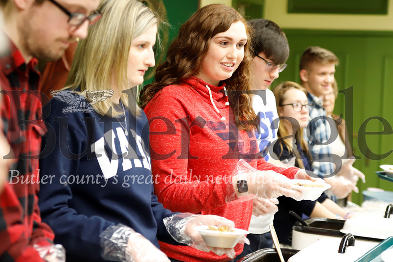 Julia Singleton (left), Mia Haher and  members of Young Adult Ministry of the Butler Area Catholic Parishes   serve dinner at St. Paul's Parish weekly dinner. Seb Foltz/Butler Eagle