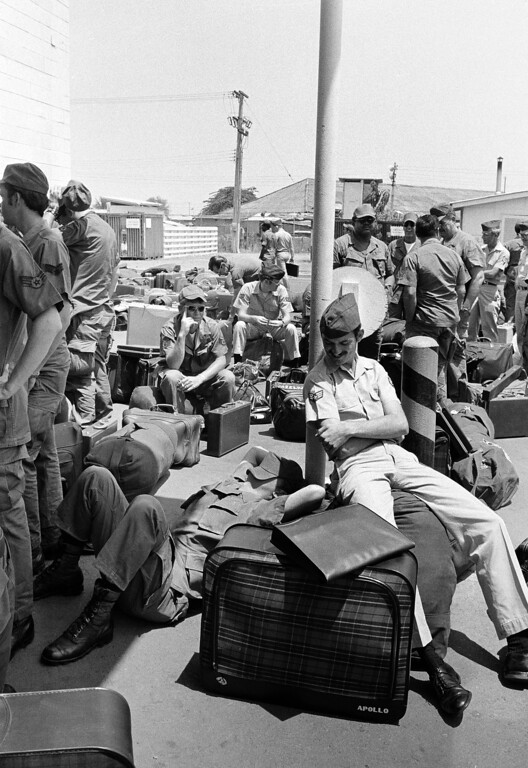 . An American GI takes a nap atop his luggage as he and other troops wait to begin outprocessing at Camp Alpha in Saigon, March 27, 1973, as withdrawal of U.S. troops resume after a 10-day dispute over POWs.  All U.S. troops are due out Thursday.  (AP Photo/Chick Harrity)