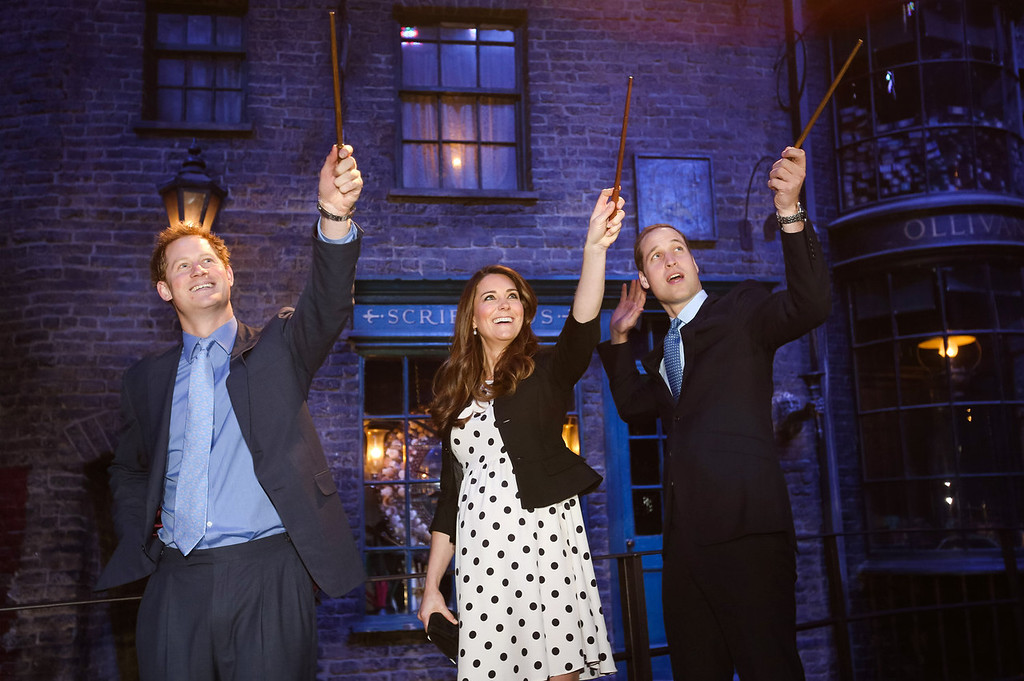 . Prince Harry, Catherine, Duchess of Cambridge and Prince William, Duke of Cambridge raise their wands on the set used to depict Diagon Alley in the Harry Potter Films during the Inauguration Of Warner Bros. Studios Leavesden on April 26, 2013 in London, England.  (Photo by Paul Rogers - WPA Pool/Getty Images)