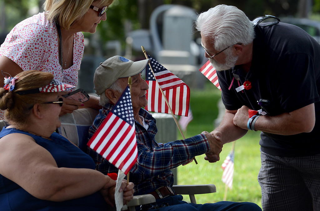 . 0528_NWS_IDB_L-POMONA-01-JCM (Jennifer Cappuccio Maher/Staff Photographer) Earl De Vries, of Ontario, right, shakes hands with WWII veteran Robert Barela, of Pomona, as his daughter Rozanne Walborn, of Ontario, top left, and niece Debra Bengoa watch during Memorial Day services Monday, May 27, 2013, at Pomona Valley Memorial Park in Pomona.