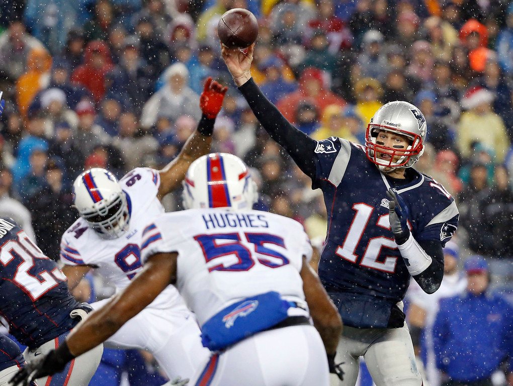. New England Patriots quarterback Tom Brady (12) passes over Buffalo Bills linebacker Jerry Hughes (55) in the first quarter of an NFL football game, Sunday, Dec. 29, 2013, in Foxborough, Mass. (AP Photo/Elise Amendola)
