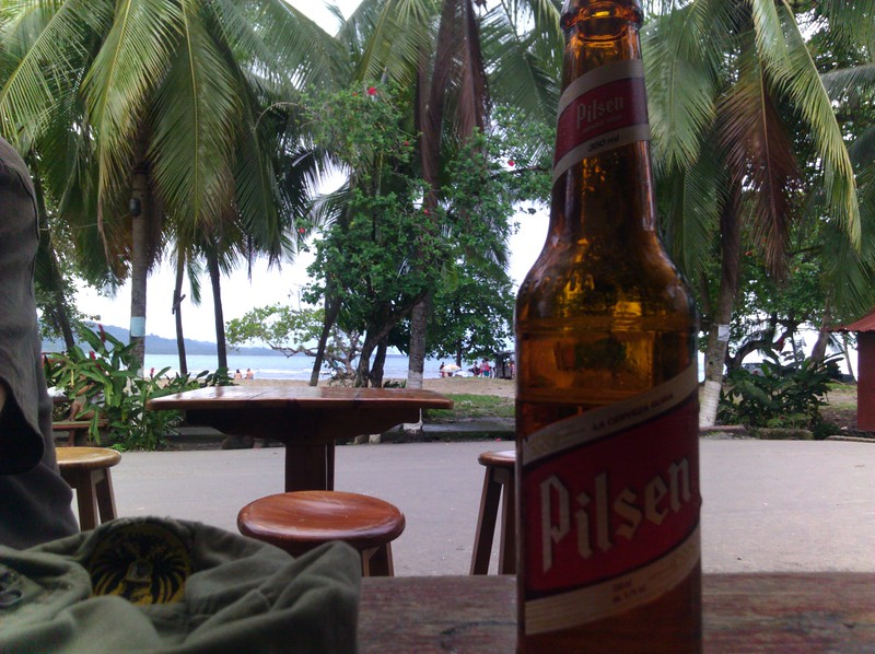 pilsen beer and the bright turquoise caribbean in the background, at Ute's bar in PV