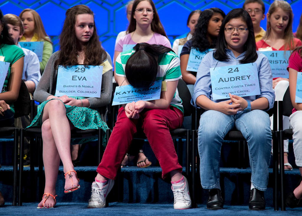 . Katharine Wang, 11, of Beijing, China, center, gathers herself before the start of the semifinal round of the National Spelling Bee, Thursday, May 30, 2013, in Oxon Hill, Md. From left are, Eva Kitlen of Niwot, Colo., Wang, and Audrey Bantug, 13, of San Ramon, Calif. (AP Photo/Evan Vucci)