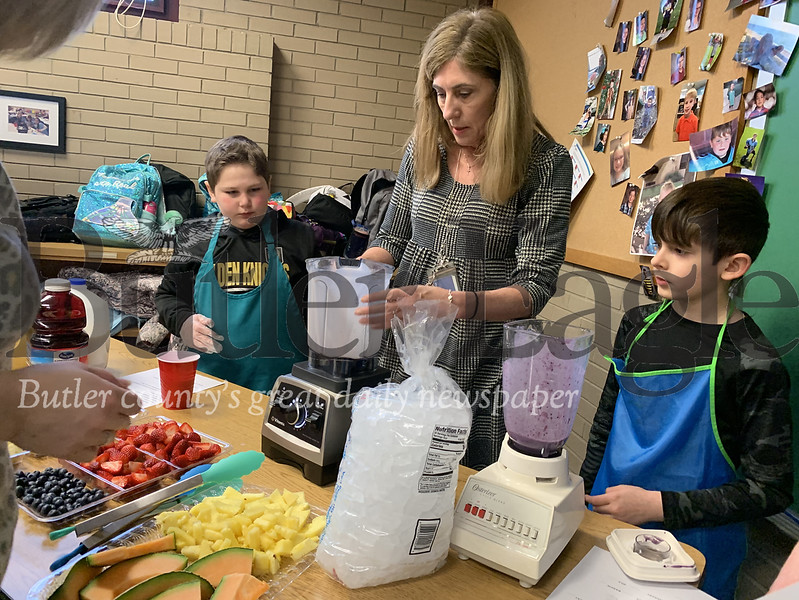 Gifted Education Teacher Rebecca Hester helps third grade students Zeke Fagan (left) and George Shattahi blend fruit for smoothies at their breakfast with cops event Wednesday morning. Photos by Alexandria Mansfield.