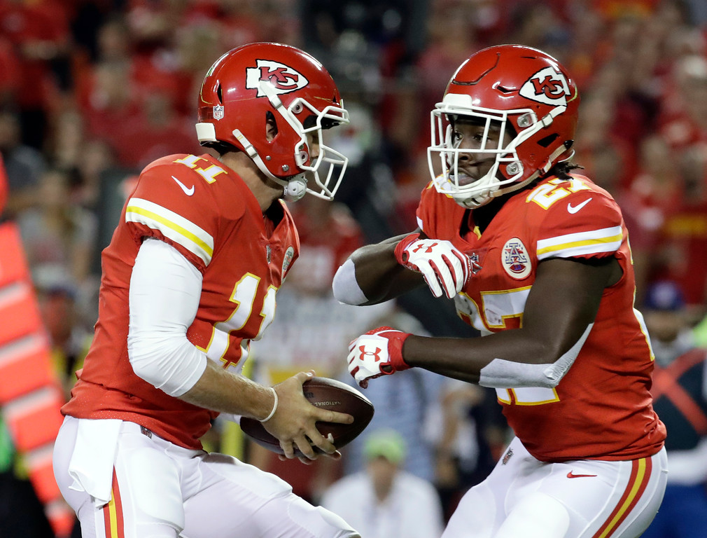 . Kansas City Chiefs quarterback Alex Smith (11) fakes a handoff to running back Kareem Hunt during the first half of an NFL football game against the Washington Redskins in Kansas City, Mo., Monday, Oct. 2, 2017. (AP Photo/Charlie Riedel)