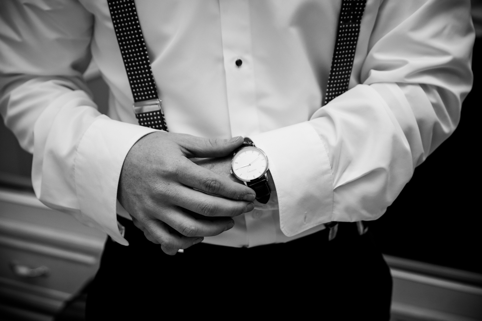 a black and white photo of a groom's hands as he is getting ready for his wedding day