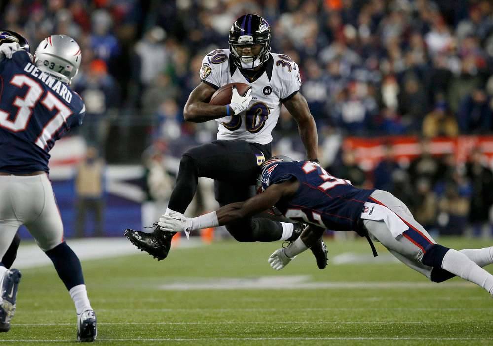 Description of . Baltimore Ravens running back Bernard Pierce (30) leaps to get away from New England Patriots free safety Devin McCourty in the third quarter of the NFL AFC Championship football game in Foxborough, Massachusetts, January 20, 2013. REUTERS/Jim Young
