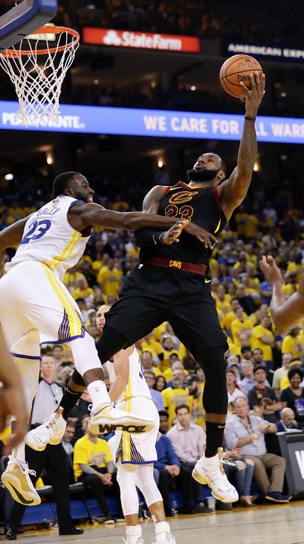 . Cleveland Cavaliers forward LeBron James, right, shoots against Golden State Warriors forward Draymond Green during the second half of Game 1 of basketball\'s NBA Finals in Oakland, Calif., Thursday, May 31, 2018. (AP Photo/Marcio Jose Sanchez)