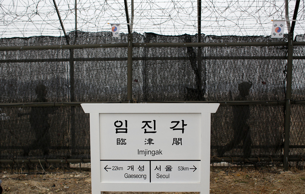 """. South Korean army soldiers patrol along a barbed-wire fence near a directional sign showing the distance to North Korea\'s Kaesong city  and South Korea\'s capital Seoul at the Imjingak Pavilion near the border village of the Panmunjom, which separated the two Koreas since the Korean War, in Paju, north of Seoul, South Korea, Friday, April 5, 2013. After a series of escalating threats, North Korea has moved a missile with \""""considerable range\"""" to its east coast, South Korea\'s defense minister said Thursday. But he emphasized that the missile was not capable of reaching the United States and that there are no signs that the North is preparing for a full-scale conflict. (AP Photo/Lee Jin-man)"""