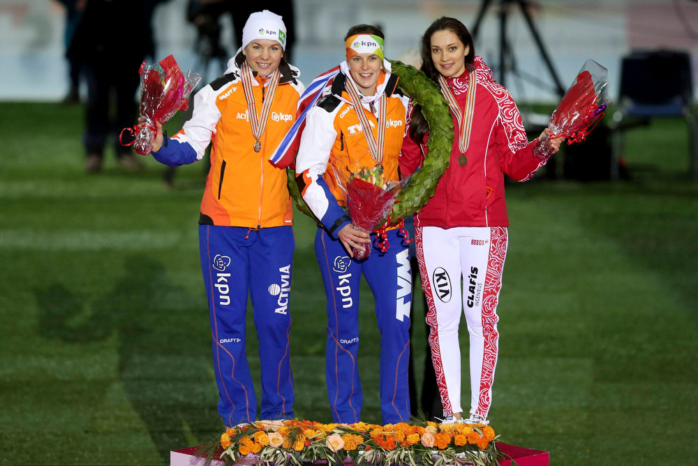 Description of . Ireen Wust of the Netherlands waves on the podium, after winning the overall women's title, next to second place winner Diane Valkenburg of the Netherlands (L) and third place winner Yekaterina Shikhova of Russia at the World Speedskating Championships in Hamar in this picture provided by NTB Scanpix February 17, 2013. REUTERS/Hakon Mosvold Larsen/NTB Scanpix