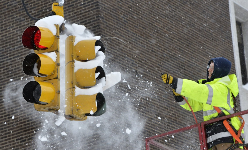 . City of Erie traffic engineering employee Chuck Carnes Jr. uses compressed air to clear snow from a traffic signal in Erie, Pa., Wednesday, Dec. 27, 2017. Carnes was part of a two-man crew clearing signals after a record-setting snowfall. (Greg Wohlford/Erie Times-News via AP)