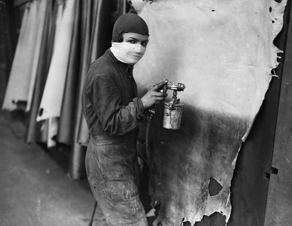 . 21st January 1932:  A worker sprays a hide at Bevingtons leather factory in Bermondsey, London. Before being made into footwear the skins are dipped into lime and water, tanned, dyed and finally sprayed.  (Photo by Fox Photos/Getty Images)