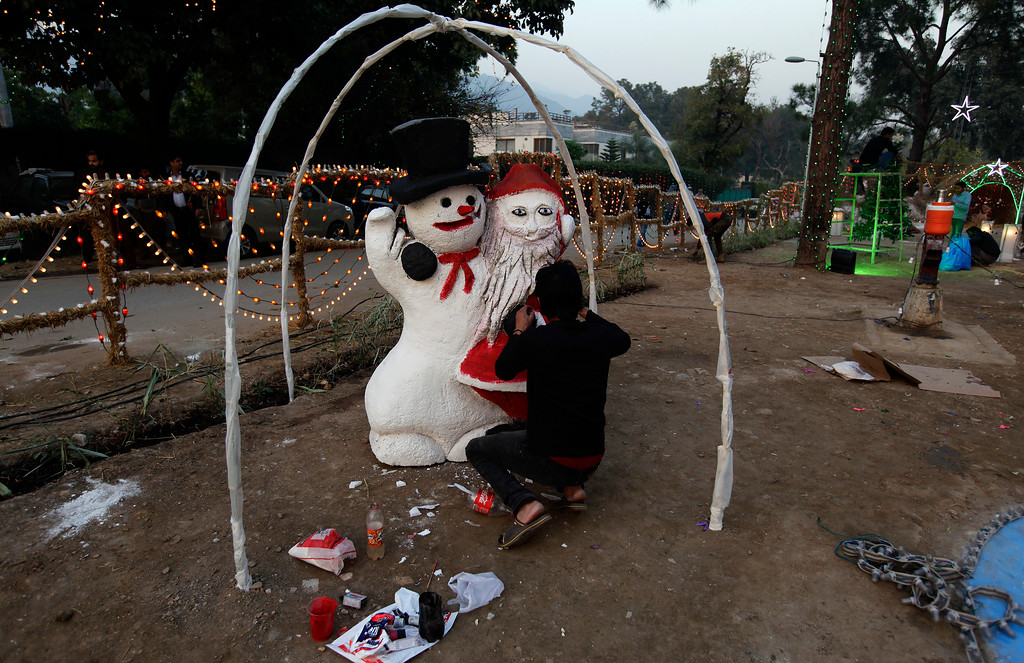 . A Christian prepares Santa Clause at an enclosure specially decorated for Christmas celebrations, at a Christian neighborhood of Islamabad, Pakistan, Sunday, Dec. 24, 2017. (AP Photo/Anjum Naveed)