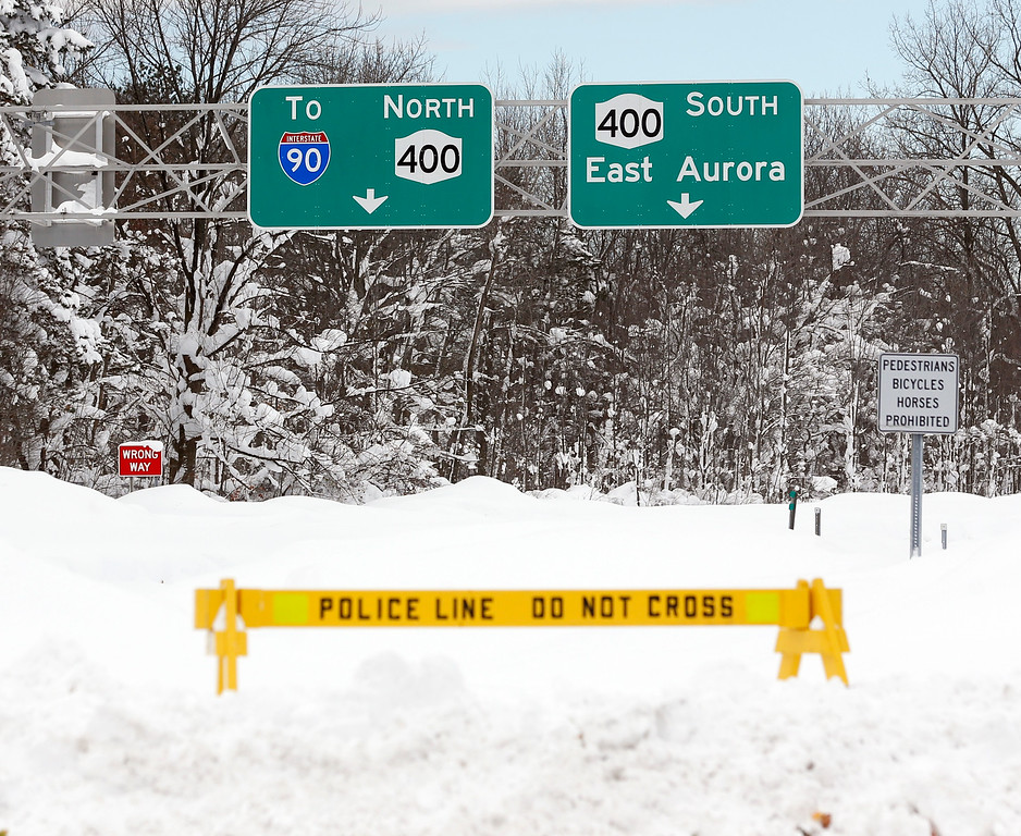 . A police barrier prevents vehicles from entering Route 400 on Thursday, Nov. 20, 2014, in West Seneca, N.Y.  A new blast of lake-effect snow pounded Buffalo for a third day piling more misery on a city already buried by an epic, deadly snowfall that could leave some areas with nearly 8 feet of snow on the ground when it\'s all done. (AP Photo/Mike Groll)