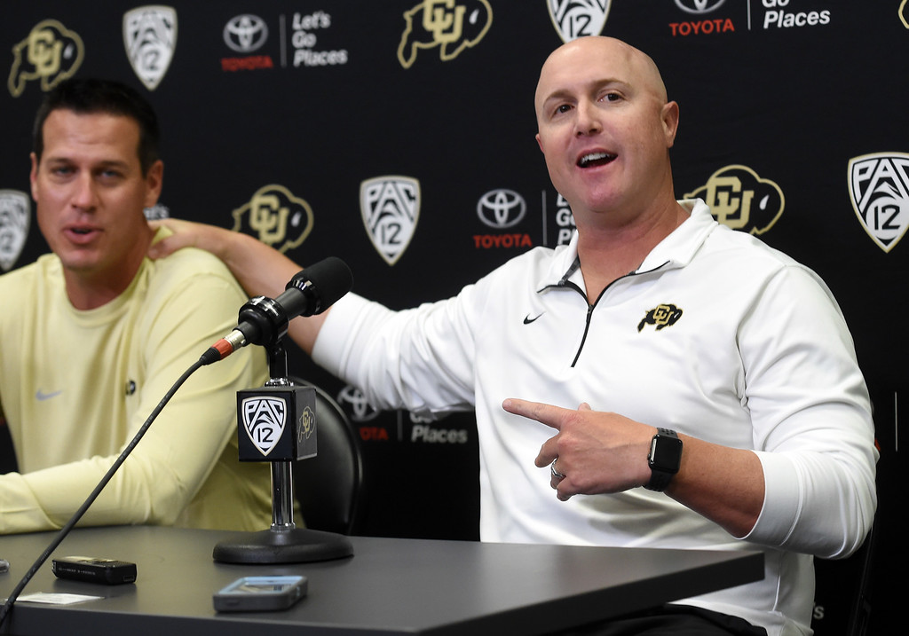 . CU defensive coordinator, D.J. Eliot, left, and OC, Darrin Chiaverini, have a moment during CU football and Fall sports media day. For more photos, go to dailycamera.com. Cliff Grassmick  Staff Photographer  August 4, 2018