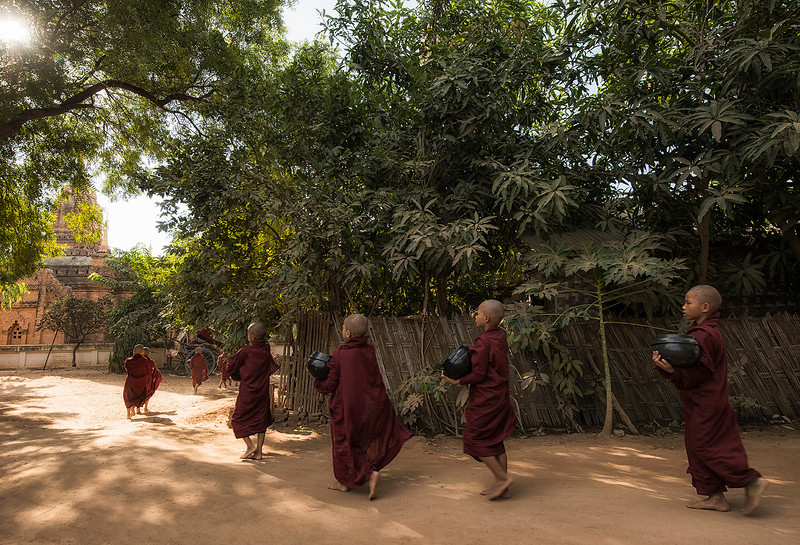 Young monks out on their morning run asking the locals for alms.  Bagan, Myanmar,2017.