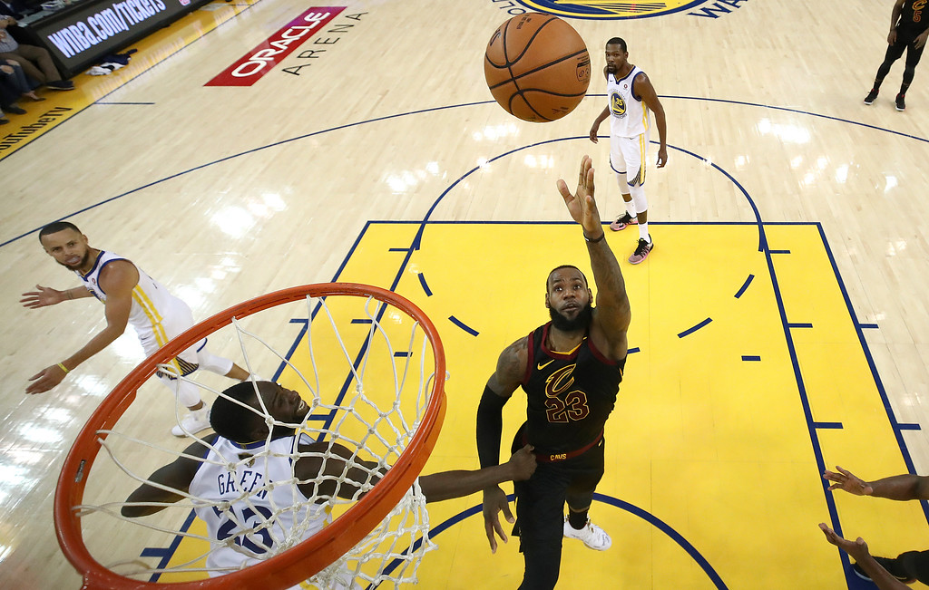 . Cleveland Cavaliers forward LeBron James, right, shoots against the Golden State Warriors during the second half of Game 1 of basketball\'s NBA Finals in Oakland, Calif., Thursday, May 31, 2018. The Warriors won 124-114 in overtime. (Ezra Shaw/Pool Photo via AP)