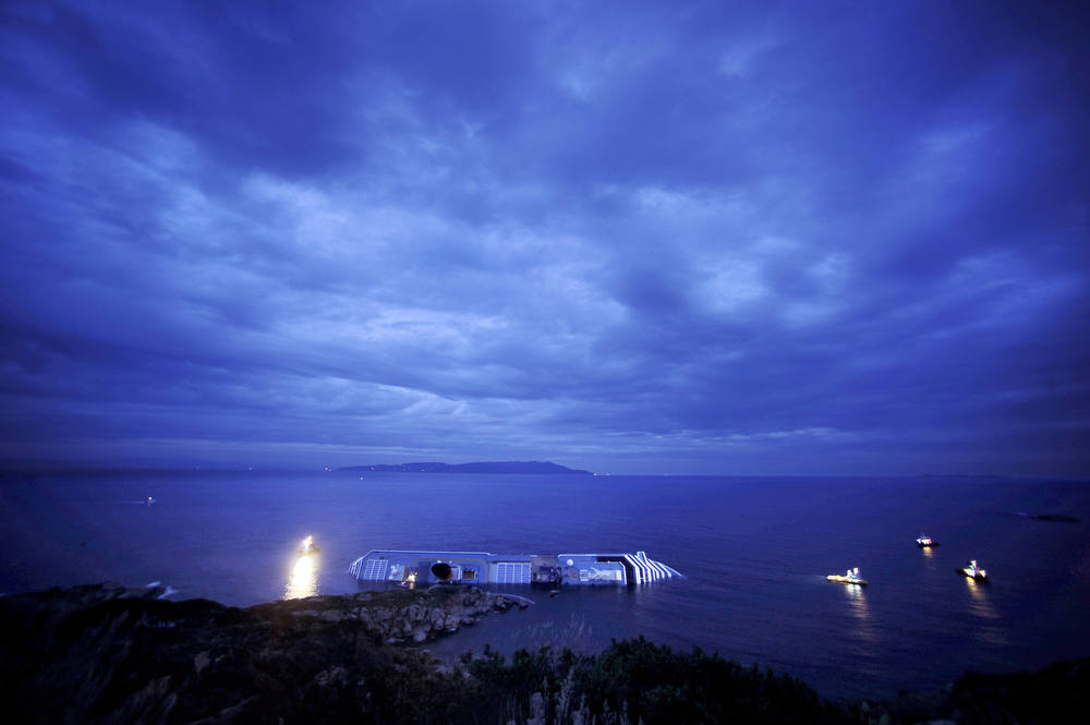Description of . Sunset on January 16, 2012, over the cruise liner Costa Concordia aground in front of the harbor of Isola del Giglio after hitting underwater rocks on January 13. Pier Luigi Foschi, head of the Costa Crociere line, said the company had commissioned several firms to look at the best way to salvage the 114,500-ton vessel lying on its side. The 290-metre (950-feet) long Costa Crociere, which is 17 decks high, has a large gash in its hull from running on to rocks before it capsized on Friday night. Coastguards said the half-submerged giant ship had now stabilized as weather conditions off the Tuscan coast improved but added that there was still a risk the hulk could slip off a rocky shelf into the open sea and sink entirely.      AFP PHOTO / FILIPPO  MONTEFORTE/AFP/Getty Images