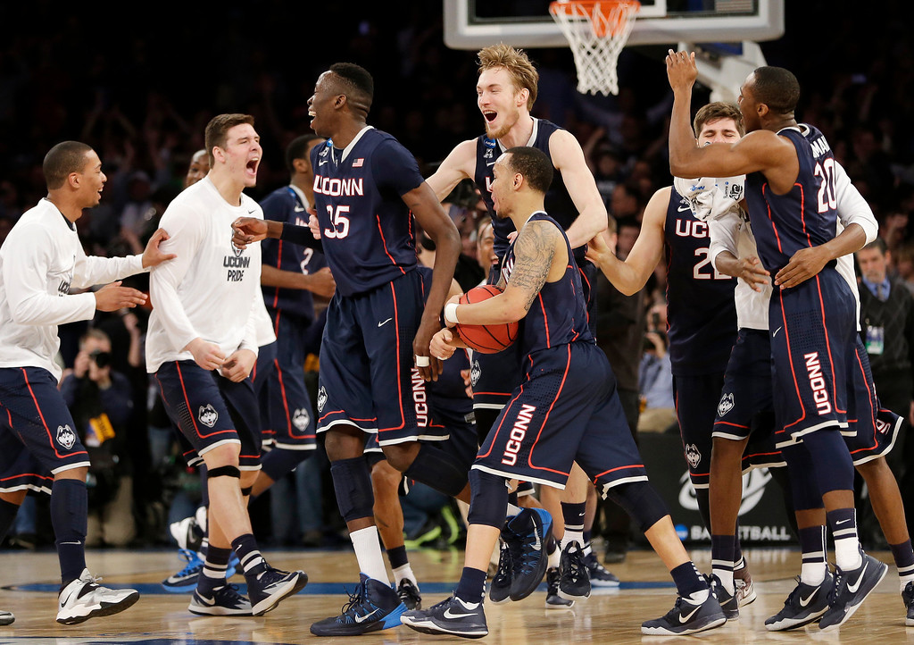. Connecticut players celebrate after beating Michigan State 60-54 in a regional final at the NCAA college basketball tournament, Sunday, March 30, 2014, in New York. (AP Photo/Seth Wenig)