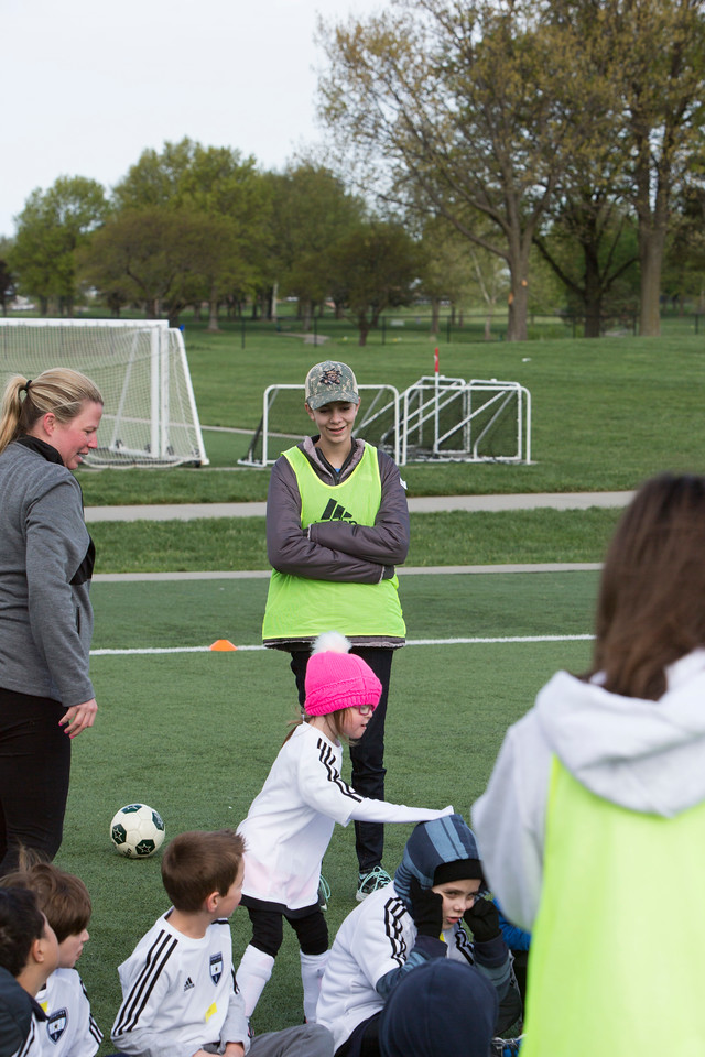 Gabby Warrender, St. Aquinas Freshman (middle -- in hat and grey coat)<br /> watches as the kids play duck duck goose
