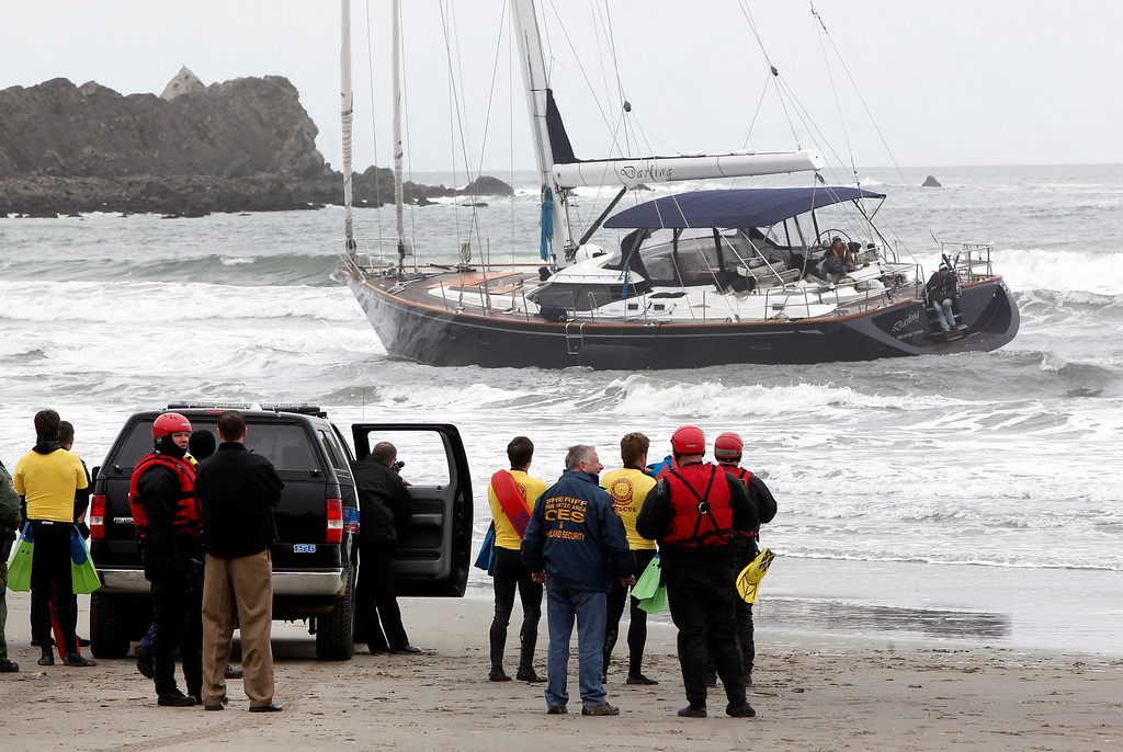 . Officials attempt to rescue three people aboard of the 82-foot-long sailboat, the Darling, stuck in the surf off Linda Mar Beach in Pacifica, Calif., Monday morning March 4, 2013. The boat had been reported stolen from a Sausalito marina earlier. The three people aboard were all rescued and arrested. (Karl Mondon Photo)