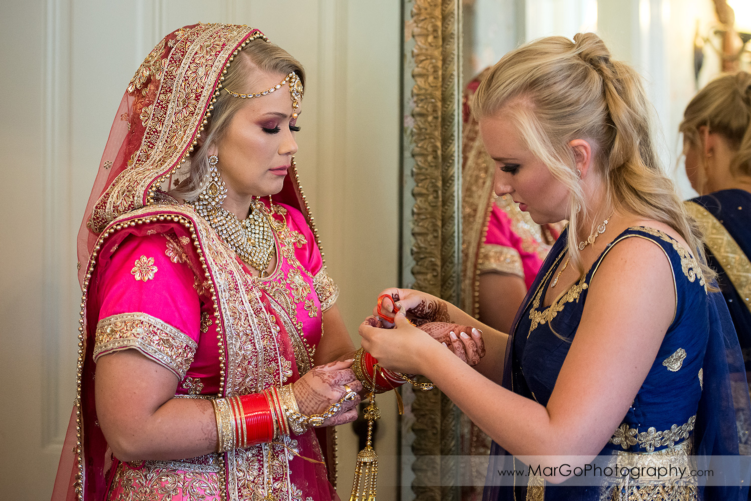 Indian bride in pink saree and her sister in blue dress before wedding ceremony at Elliston Vineyards in Sunol
