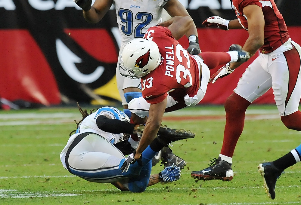 . William Powell #33 of the Arizona Cardinals is upended by Louis Delmas #26 of the Detroit Lions at University of Phoenix Stadium on December 16, 2012 in Glendale, Arizona. Arizona won 38-10. (Photo by Norm Hall/Getty Images)