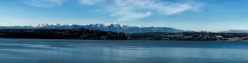 """08 Dec 14.  A couple days post snowfall I headed out to a good friend's home which has a nice view of the Olympic Mountains looking west across Hood Canal. The weather was just a bit hazy but nothing that couldn't be corrected in software. I took several shots with the idea of creating a panorama taking in the entire range. This is what we have for today, a composite of 5 images with a little cropping for aesthetics. I've added in a small amount of grain to give the water and mountains a somewhat more realistic look, as neither of them are really smooth as they all too often appear in a two dimensional representation of a three dimensional object. The amount of grain you """"see"""" will be dependent on your screen/graphics card combo. Aside from the cropping and grain, this is pretty much what the camera captured. Nikon D300s; 18 - 200; Aperture Priority; ISO 200; 1/500 sec @ f /11."""