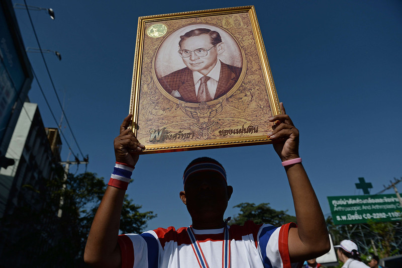 """. A Thai anti-government protester holds up a framed portrait of King Bhumibol Adulyadej as protesters march through the streets of Bangkok in a move to \'shut down\' the city on January 13, 2014. Thai opposition protesters launched their attempted \""""shutdown\"""" of Bangkok on January 13, occupying key intersections in the capital in an escalation of their campaign to unseat Prime Minister Yingluck Shinawatra. (CHRISTOPHE ARCHAMBAULT/AFP/Getty Images)"""