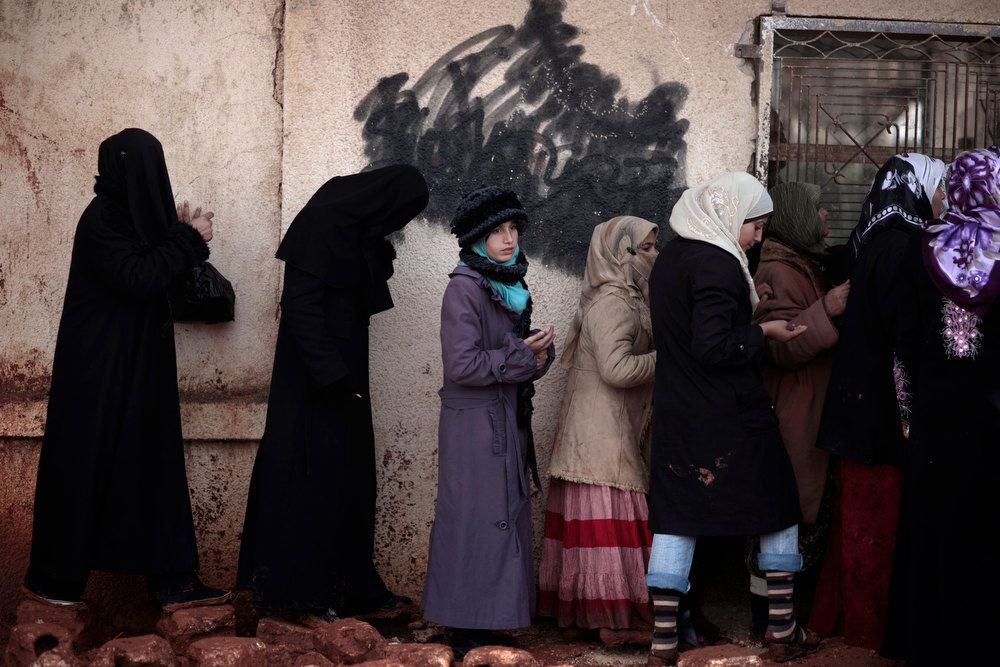 . Syrian women wait outside a bakery shop to buy bread in Maaret Misreen, near Idlib, Syria, Wednesday, Dec. 12, 2012. (AP Photo/Muhammed Muheisen)