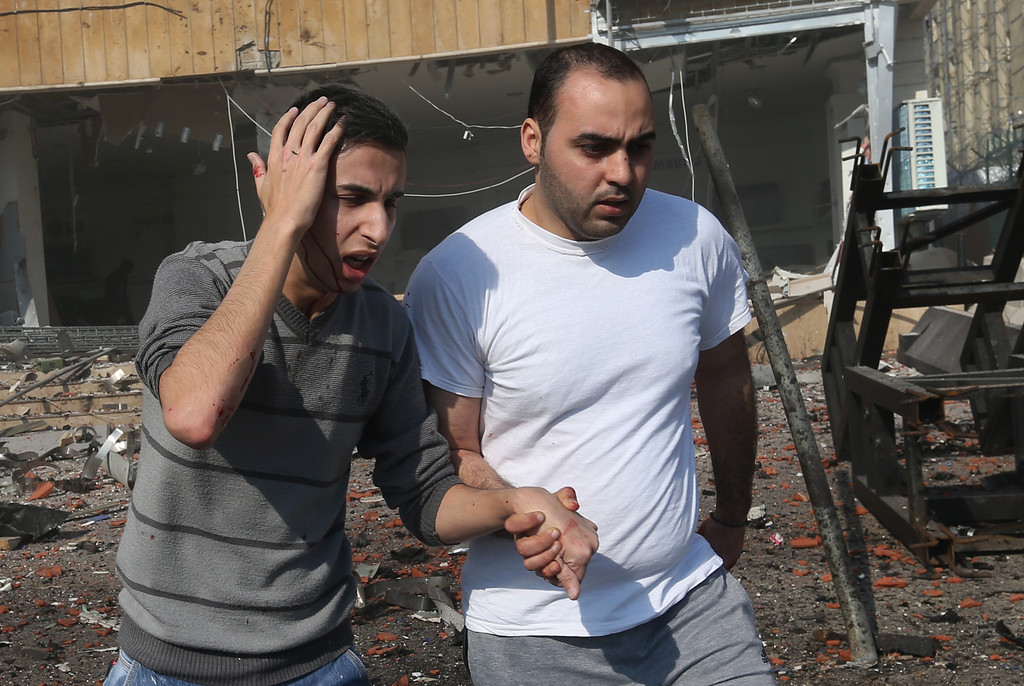 . A wounded Lebanese man is assisted at the site of an explosion, in the suburb of Beir Hassan, Beirut, Lebanon, Wednesday Feb. 19, 2014. (AP Photo/Hussein Malla)