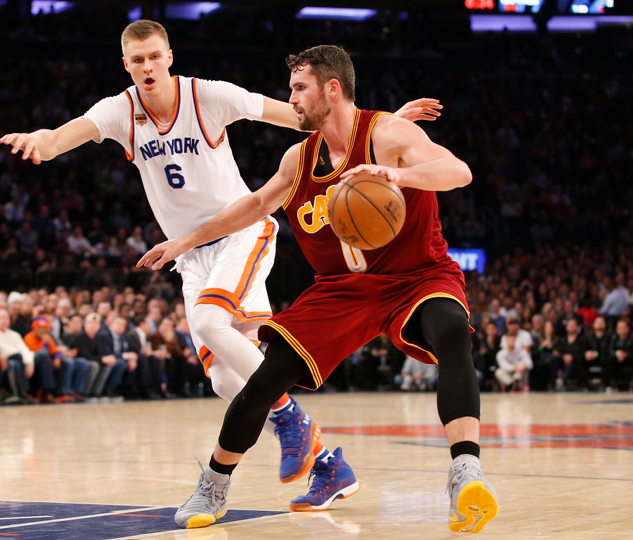 . New York Knicks forward Kristaps Porzingis (6) defends Cleveland Cavaliers forward Kevin Love (0) in the first quarter of an NBA basketball game at Madison Square Garden in New York, Wednesday, Dec. 7, 2016. The Cavaliers defeated the Knicks 126-94. (AP Photo/Kathy Willens)