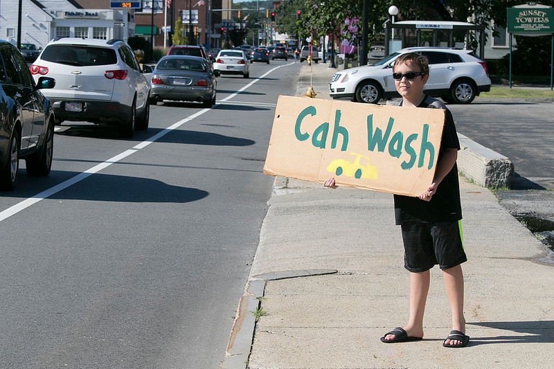 St. Leo's of Leominster Boy Scout Troop 11 held a car wash on Saturday, August 24, 2019 in the parking lot of St. Leo's. Boy Scout Sean Joffrion, 11, holds a sign on the side of the road to tell people about the fundraiser. SENTINEL & ENTERPRISE/JOHN LOVE