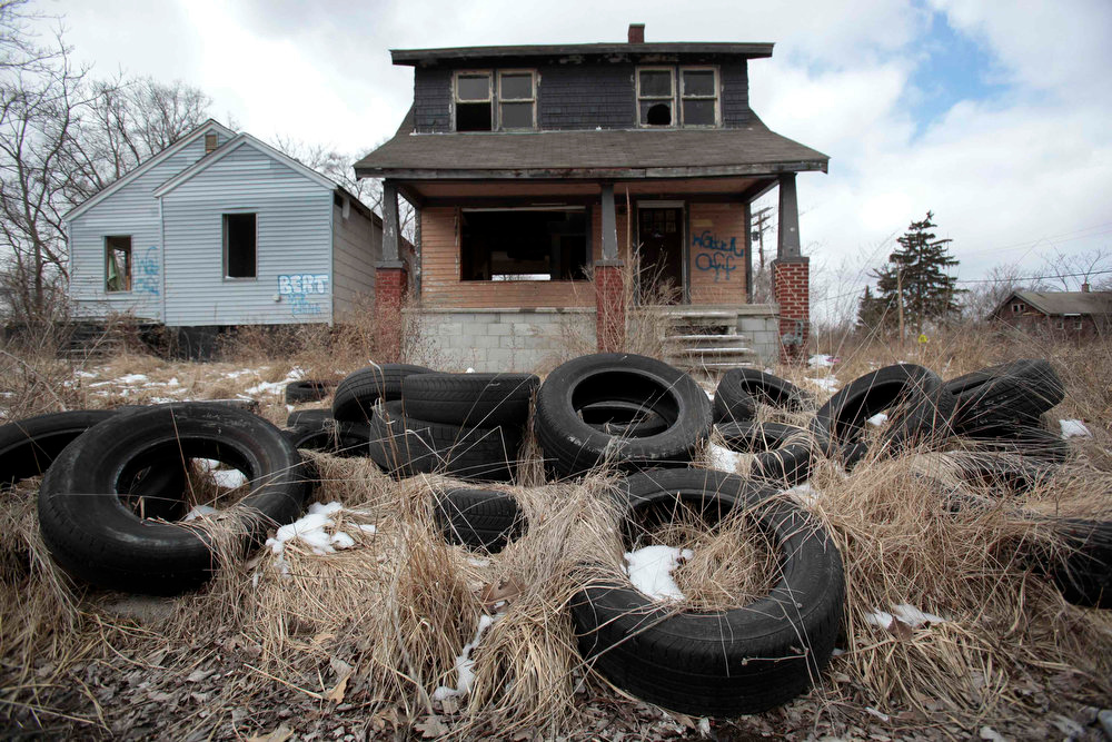 . Ilegally dumped tires sit in front of a vacant, blighted home in a once thriving neighborhood on the east side of Detroit, Michigan March 20, 2013.  When the state-imposed manager of Detroit, Kevyn Orr, begins the job on Monday he will wade into a city of crumbling neighborhoods where police fail to respond to some calls, arson fires burn out of control, and residents scour charred buildings for scrap metal to sell. Picture taken March 20, 2013.  REUTERS/ Rebecca Cook