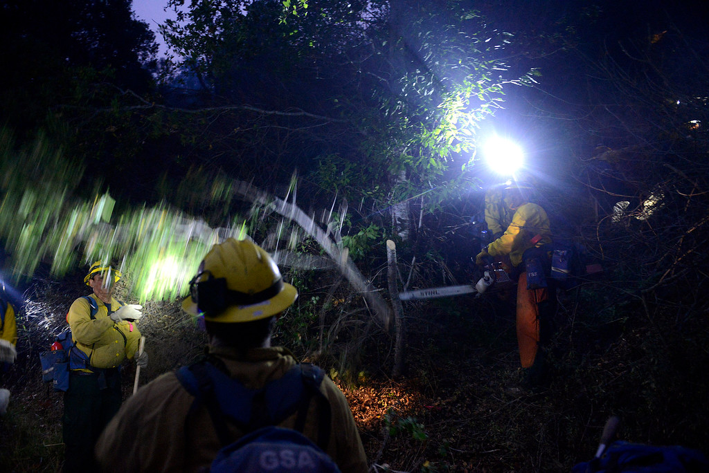 . A fire crew from Sequoia cut limbs as they head up off Highway 1 as dusk falls to battle the fire near the Big Sur Station from the Pfeiffer Ridge area in Big Sur, Calif. on Tuesday December 17, 2013. (Photo David Royal/ Monterey County Herald)
