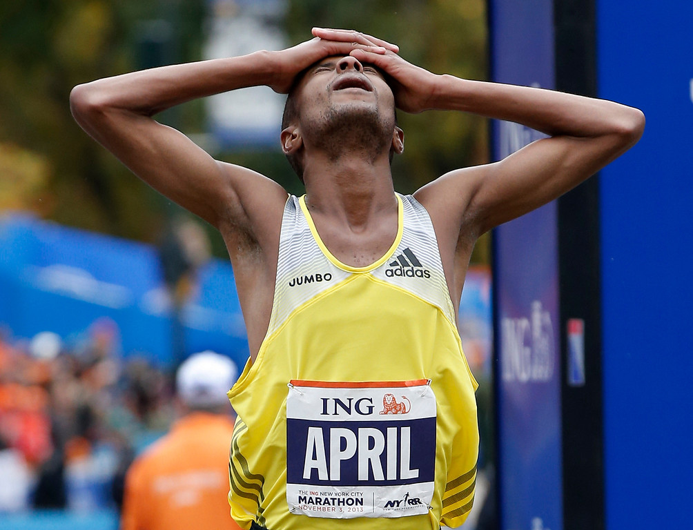 . Third-placed Lusapho April, of South Africa, reacts after finishing the New York City Marathon, Sunday, Nov. 3, 2013, in New York. (AP Photo/Kathy Willens)