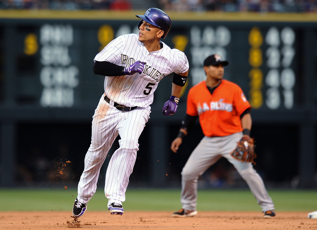. Colorado Rockies\' Carlos Gonzalez advances to third base on a single byTroy Tulowitzki in the fourth inning of a baseball game against the Miami Marlins on Tuesday, July 23, 2013, in Denver. (AP Photo/Chris Schneider)
