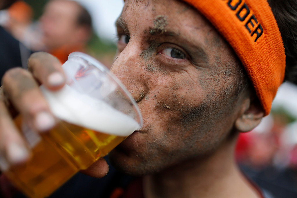 ". A participant of the ""Tough Mudder\"" endurance event series drinks a beer after crossing the finish line in the Fursten Forest, a former British Army training ground near the north-western German city of Osnabrueck July 13, 2013. The hardcore but un-timed event over 16 km (10 miles) was designed by British Special Forces to test mental as well as physical strength. Some 4,000 competitors had to overcome obstacles of common human fears, such as fire, water, electricity and heights.   REUTERS/Wolfgang Rattay"