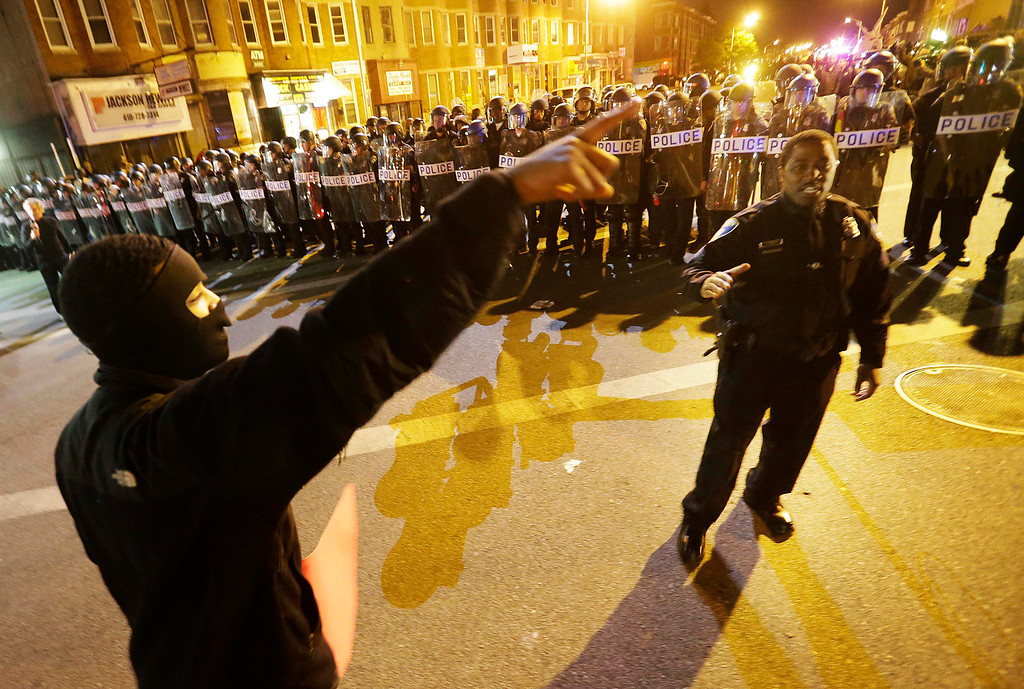 . A protester at left argues with a policeman as police line up in riot gear in the background after a 10 p.m. curfew went into effect Thursday, April 30, 2015, in Baltimore. The curfew was imposed after unrest in the city over the death of Freddie Gray while in police custody. (AP Photo/David Goldman)