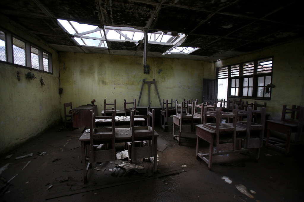 . In this Oct 17, 2014, photo, chairs rest on tables in an empty classroom at an elementary school in the abandoned village of Simacem, North Sumatra, Indonesia. The village was abandoned after its people were evacuated following the eruption of Mount Sinabung. (AP Photo/Binsar Bakkara)
