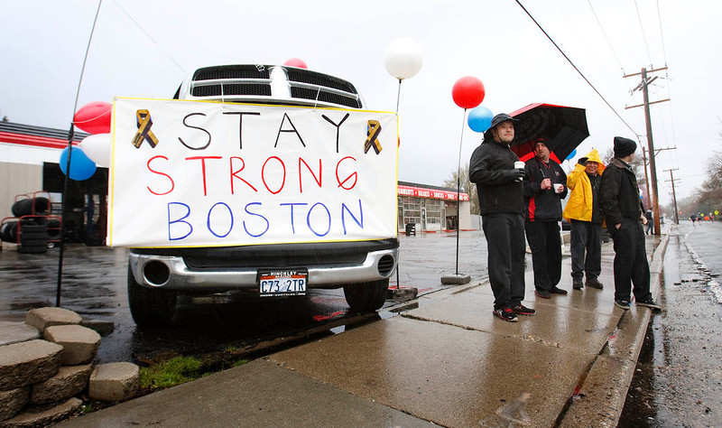 . From left, Ruben Lopez, Josh Eoff, Andres Martinez and Paul Begg stand next to a sign about the Boston Marathon explosions, outside the tire store where they work near Mile 8 of the Salt Lake City marathon on Saturday, April 20, 2013, in Salt Lake City. (AP Photo/The Salt Lake Tribune, Leah Hogsten)