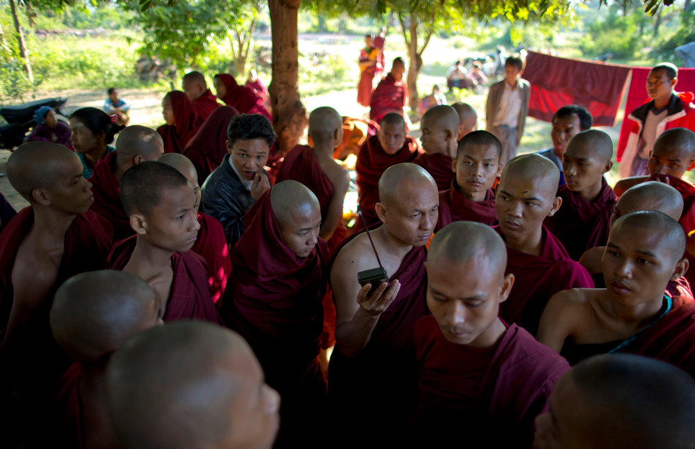. Buddhist monks,  some of who escape from the security forces crack down,  listen to radio news cast from a monastery in Monywa, northwestern Myanmar, Thursday, Nov. 29, 2012.  Security forces cracked down on protesters occupying a copper mine early Thursday, using water cannons and other devices to break up the rally hours before opposition leader Aung San Suu Kyi was expected to hear their grievances.  (AP Photo/Gemunu Amarasinghe)