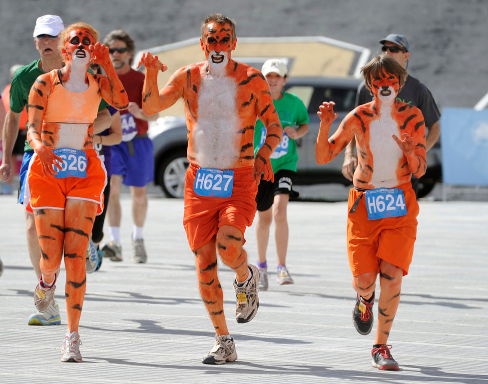 . From left to right are the Dinneen\'s from Littleton, Kelly, left, Ryan, center, and Peter, right. The 35th BolderBoulder 10k classic takes place on the streets of Boulder finishing at Folsom Field at the University of Colorado. (Photo By Kathryn Scott Osler/The Denver Post)