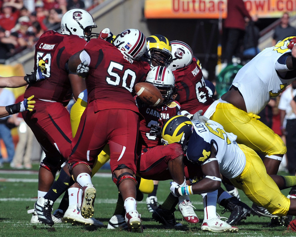 . Running back Kenny Miles #31 of the South Carolina Gamecocks fumbles in the second quarter  against the Michigan Wolverines in the Outback Bowl January 1, 2013 at Raymond James Stadium in Tampa, Florida.  (Photo by Al Messerschmidt/Getty Images)