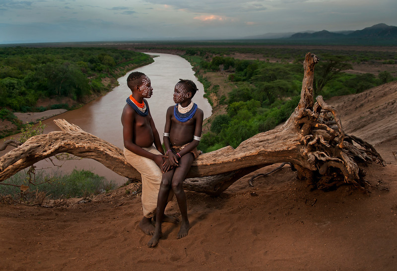 These are Gubi and Balo, two girls from the Karo tribe.The Karo, are a small tribe with an estimated population between 1,000 and 3,000. They are closely related to the Kwegu tribe. They live along the east banks of the Omo River in southern Ethiopia.The main subsistence crops of the Karo are sorghum, maize and beans, supplemented by bee-keeping and more recently fishing. Mainly river bank cultivation is the most important source of grain production, they also plant fields using rain and flood retreat water.